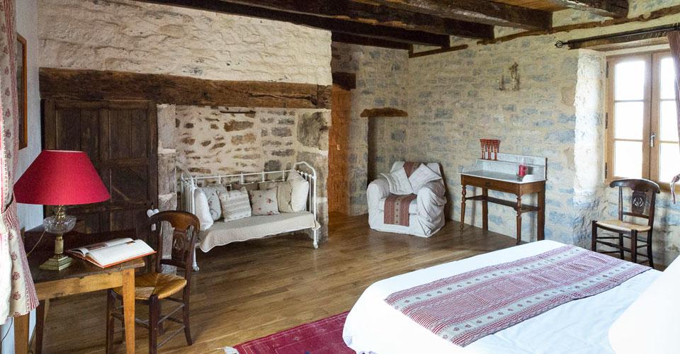 chambre colonjac avec parquet bois poutres ancestrales mur juste sablé